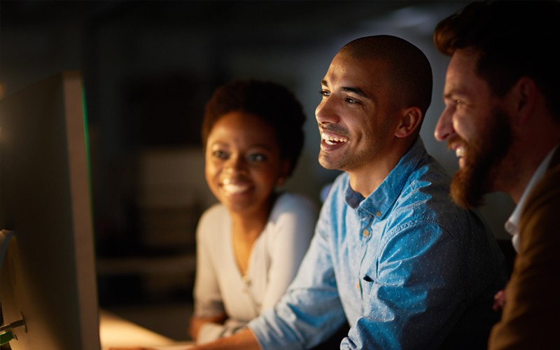 Digital collaboration three people staring into a screen and smiling